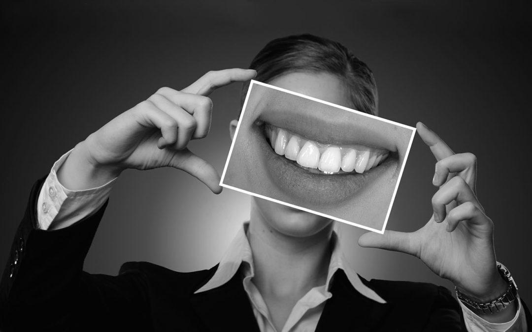 Frau hält Foto von gesunden Zähnen